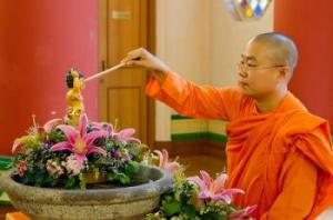 En munk badar Buddha