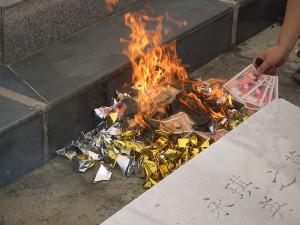 Låtsaspengar eldas på en kyrkogård i Kina. Foto Vmenkov